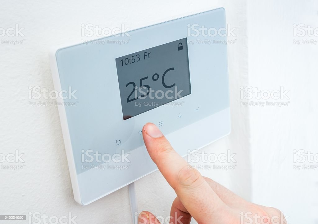 Heating concept. Adjusting temperature on digital central thermostat control. stock photo
