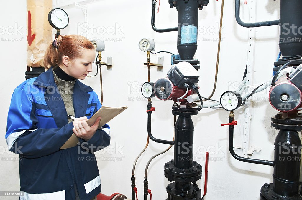 A heating engineer in boiler room recording some data royalty-free stock photo