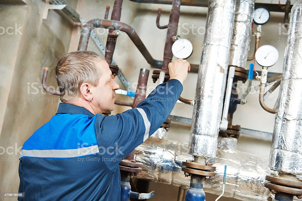 A heating engineer repairing valves and pipes in boiler room stock photo