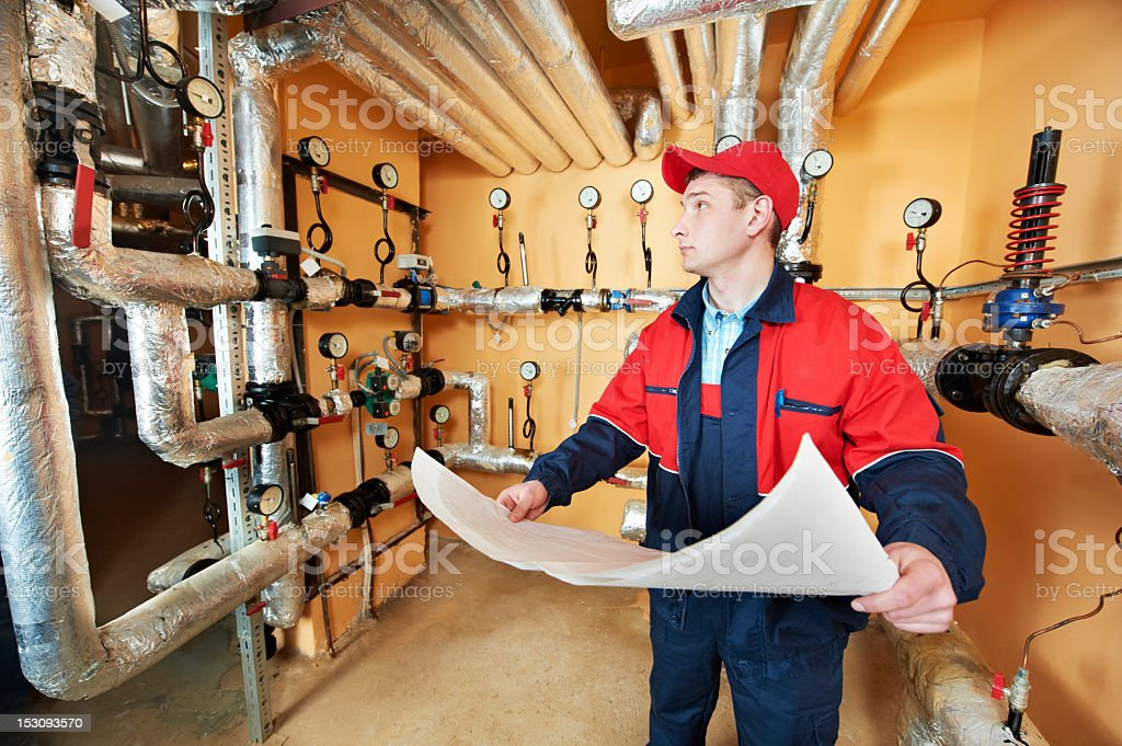 Heating engineer repairman in boiler room looking at papers stock photo