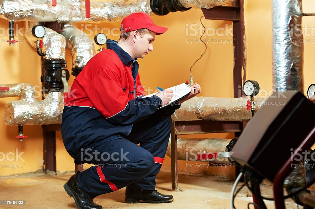 heating engineer repairman in boiler room stock photo