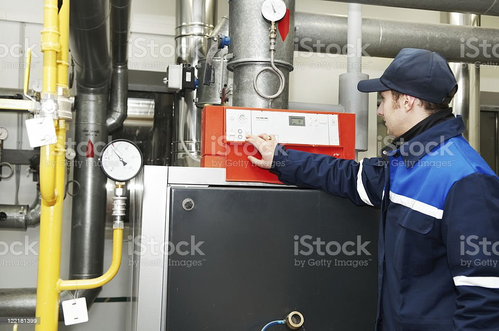 Heating engineer repairman working in a boiler room royalty-free stock photo