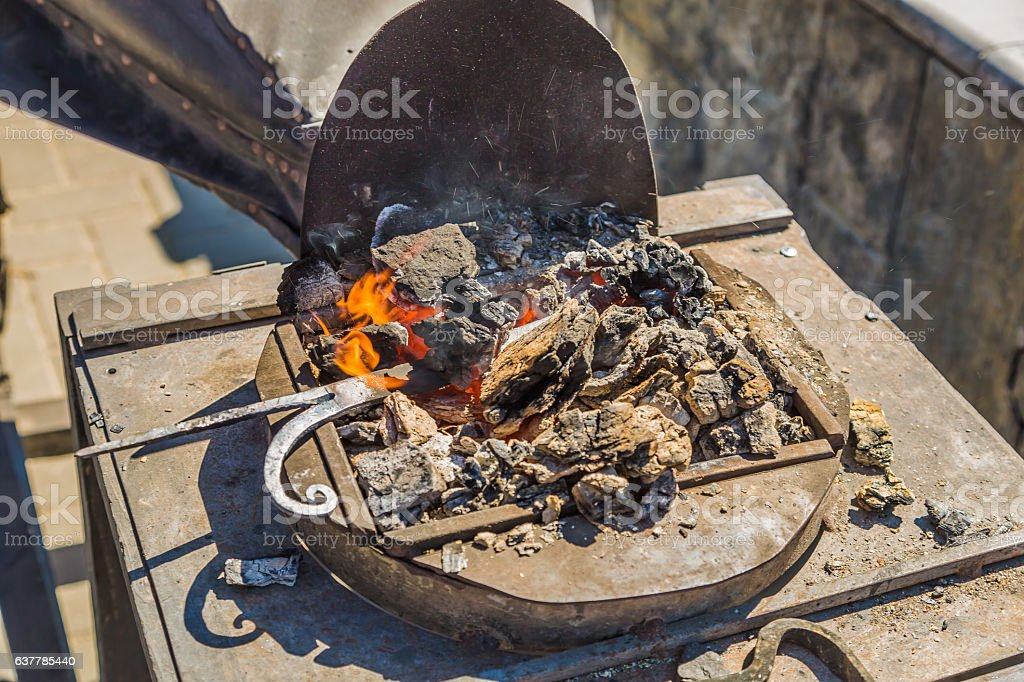 Heating of the metal in the forge on the coals stock photo