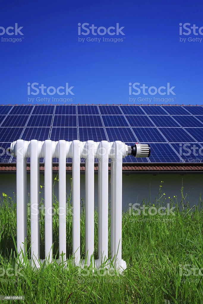 Heating radiator in front of solar panels royalty-free stock photo