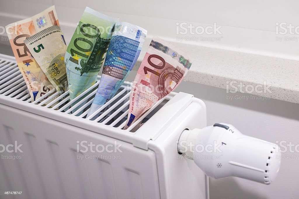heating thermostat with money stock photo