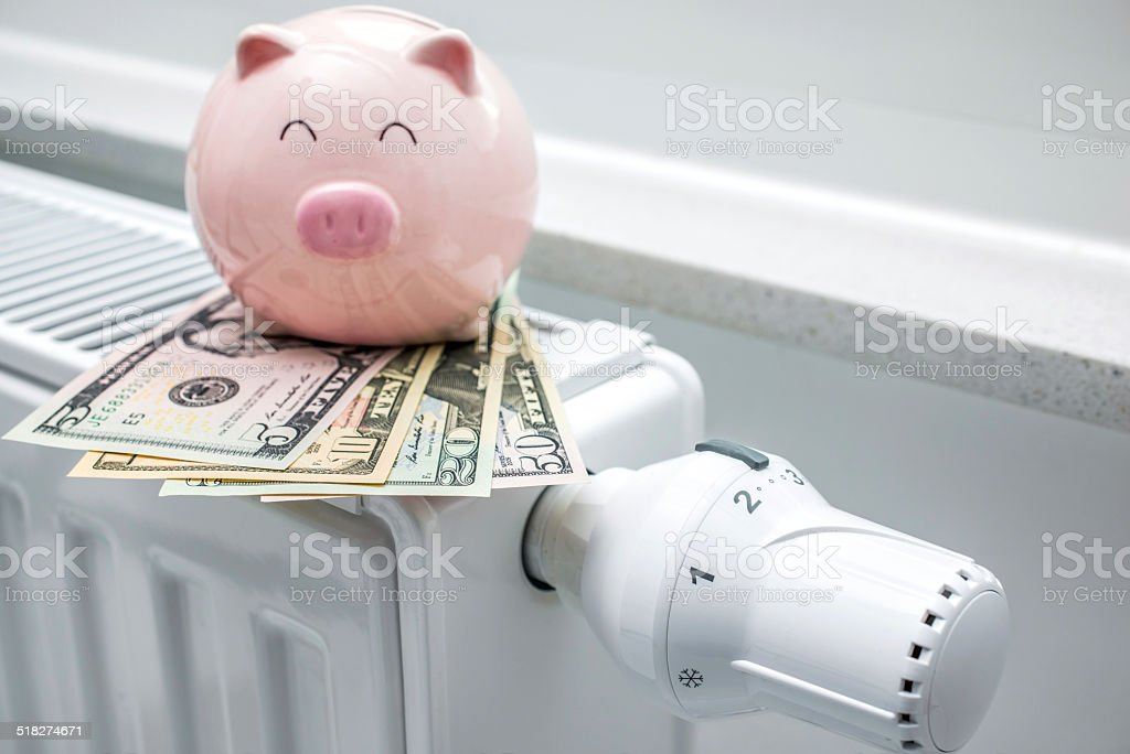 Heating thermostat with piggy bank and money stock photo