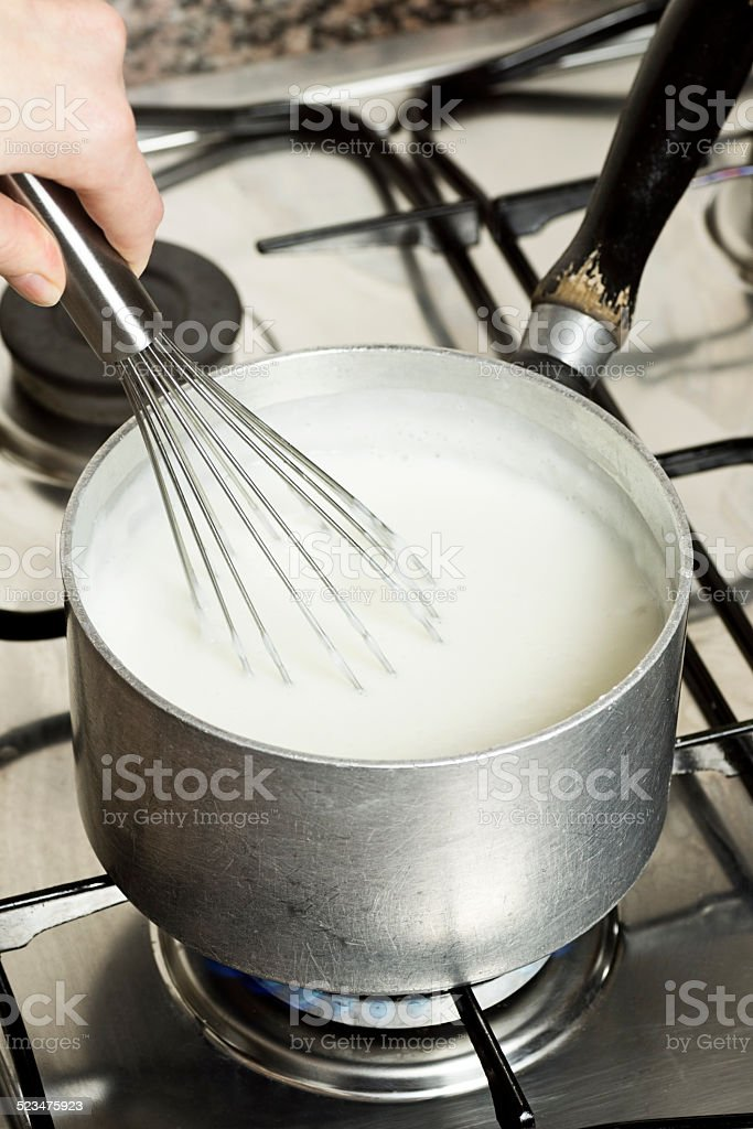 Heating Up Milk On a Stove and Stirring With Whisk stock photo