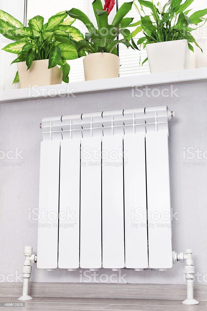 Heating white radiator with flower and window. stock photo