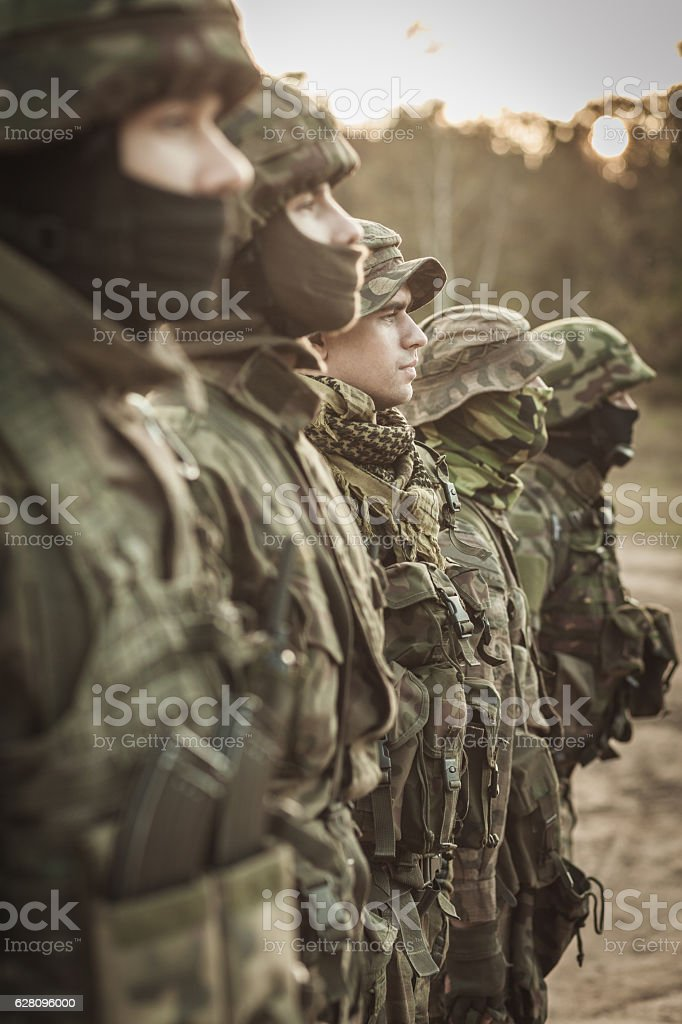 Heavily armed soldiers in a row stock photo