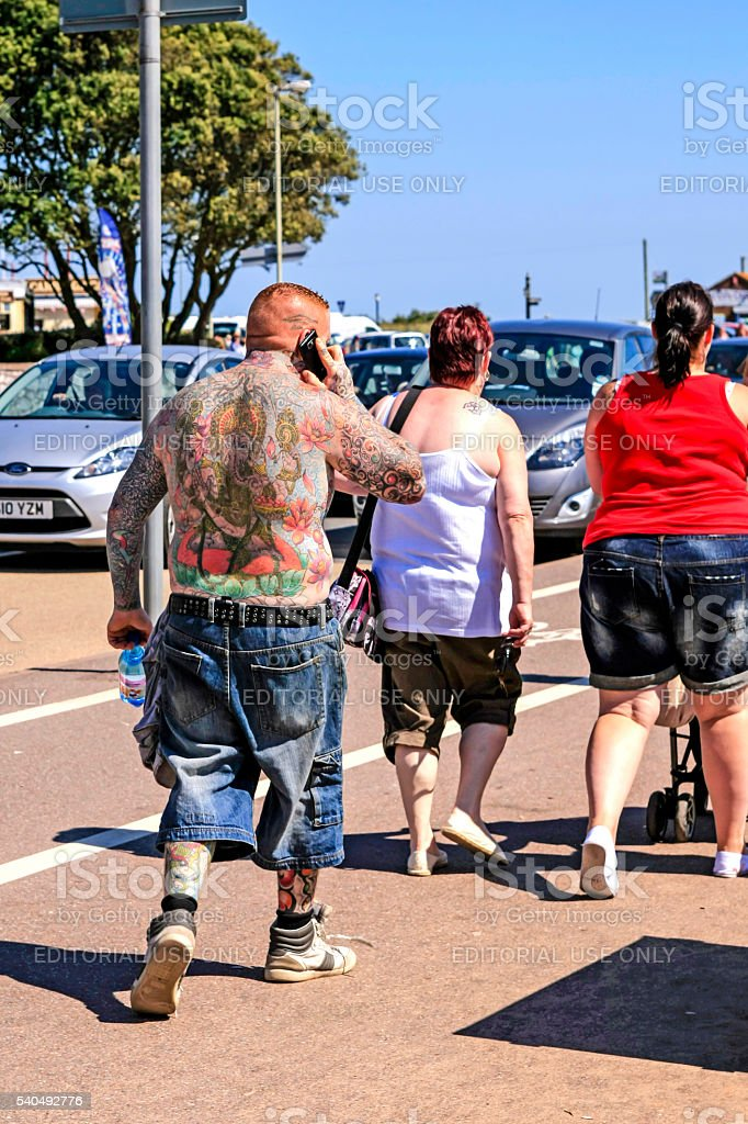 Heavily tattoed man walking in Exmouth UK stock photo
