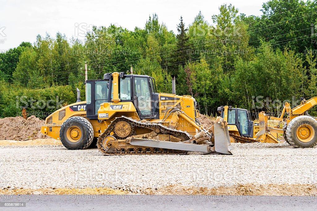 Heavy bulldozer loading and moving gravel on road stock photo