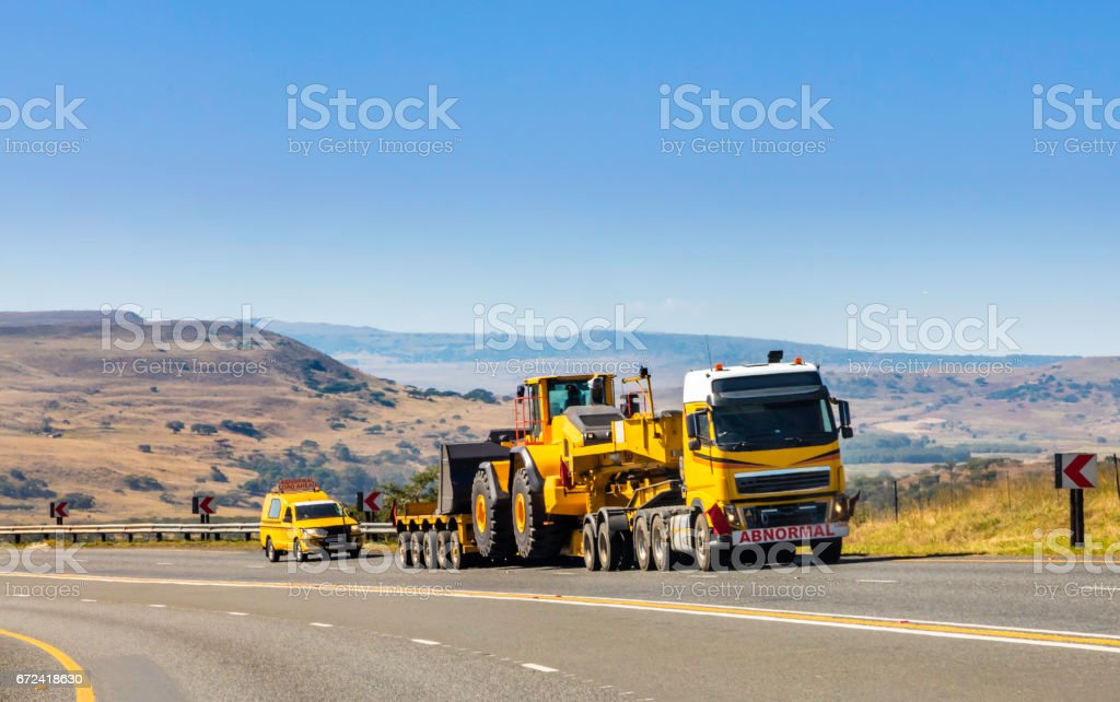 Heavy Cargo on the Road transporting construction machinery stock photo
