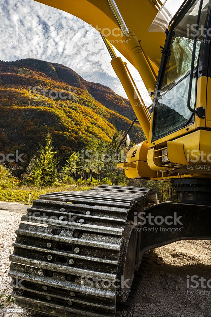 Heavy construction machinery (backhoe) in front of forest and sky stock photo