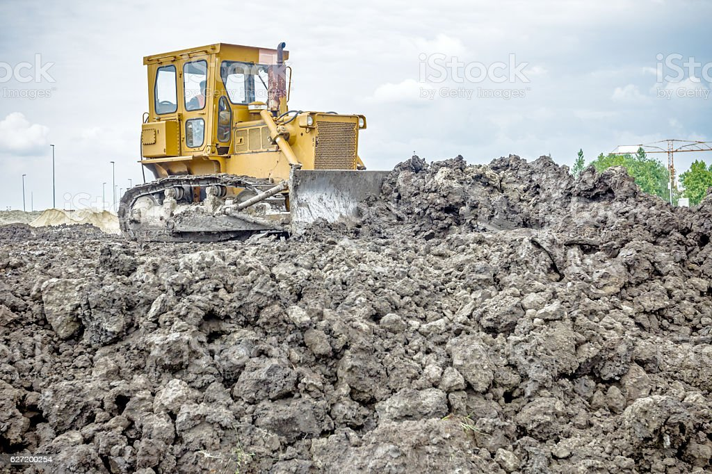 Heavy earthmover construction machine is moving earth at buildin stock photo