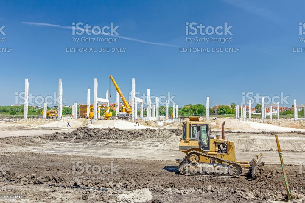 Heavy earthmover construction machine is moving earth at building site stock photo
