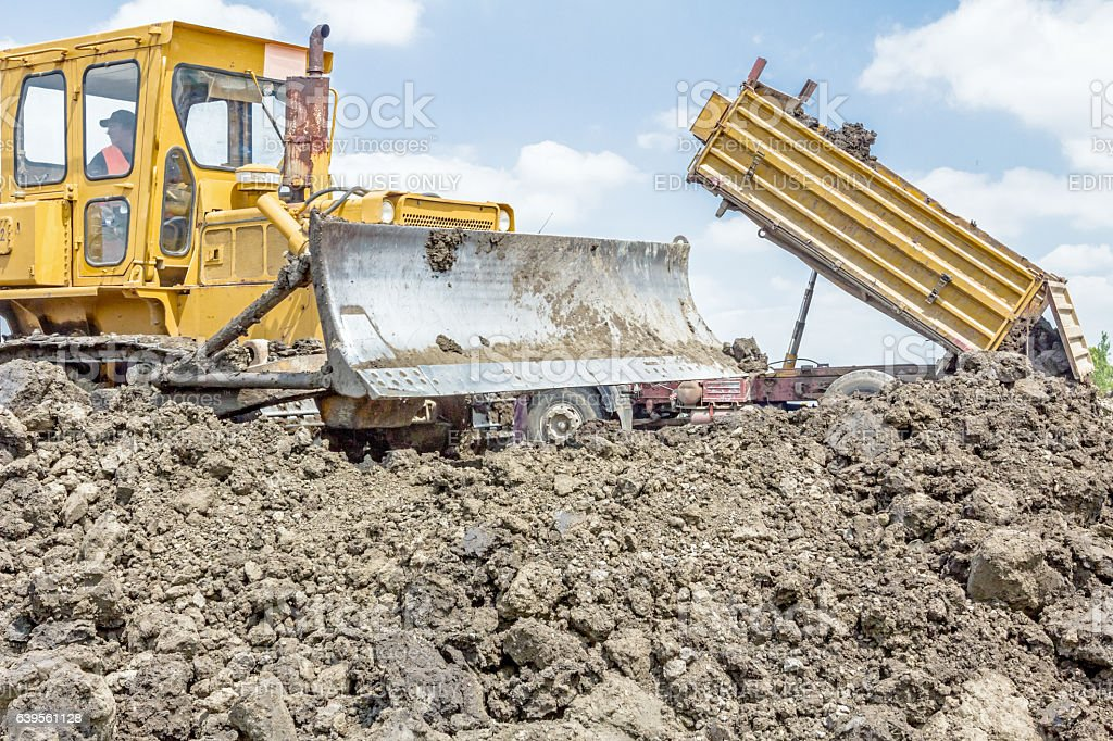 Heavy earthmover is moving earth at building site. stock photo