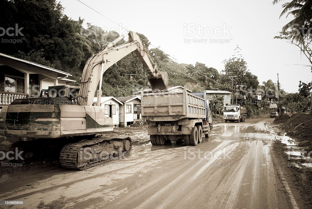 heavy equipment and dumptruck on muddy road at work stock photo