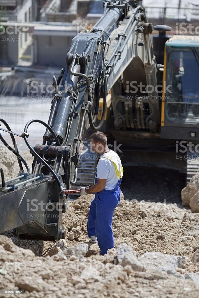 Heavy equipment mechanic  repairing excavators  in construction site royalty-free stock photo