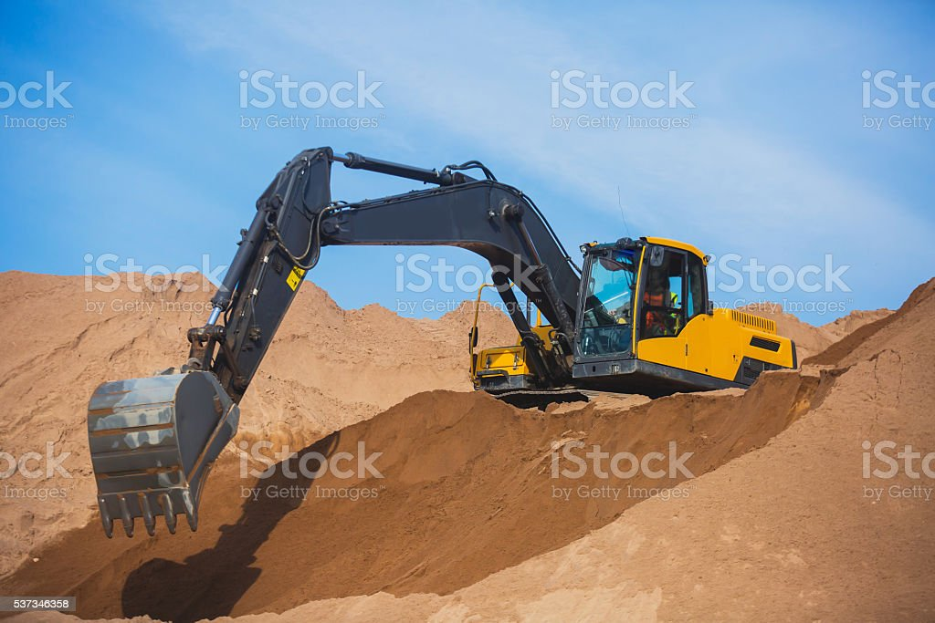 Heavy excavator and bulldozer unloading road metal during road work stock photo