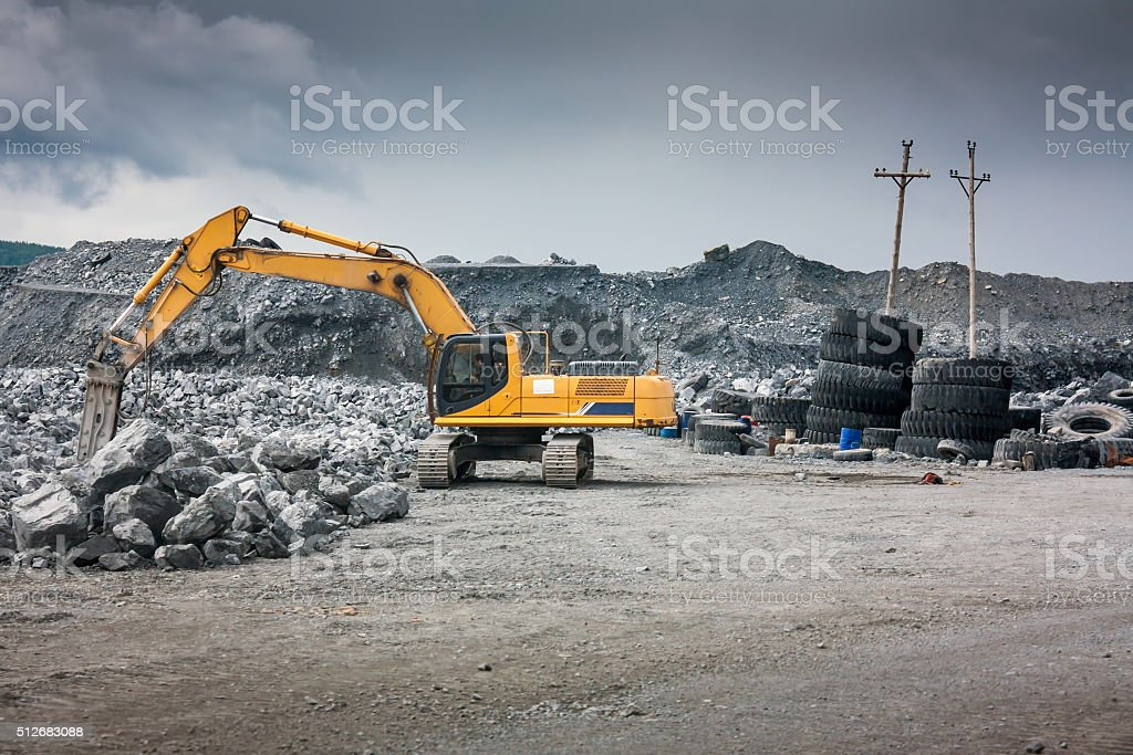 Heavy excavator with shovel standing on hill with rocks stock photo