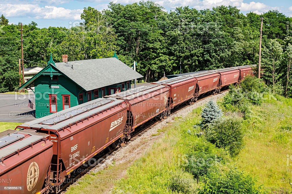 Heavy grain train passing through small rural town stock photo