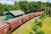 Heavy grain train passing through small rural town