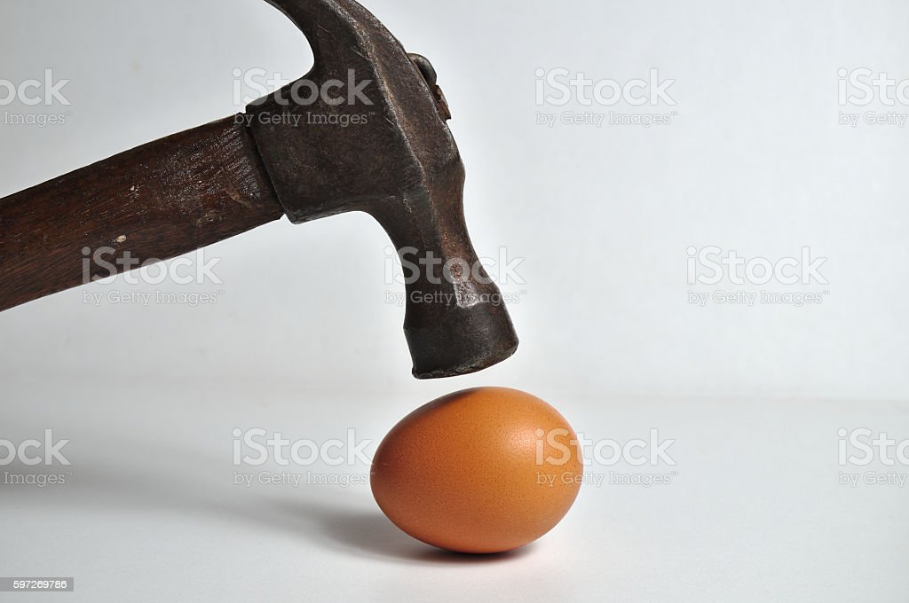 Heavy hammer on the way to crash an egg stock photo