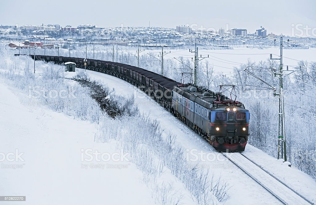 Heavy iron ore train departs city in Arctic Circle winter stock photo