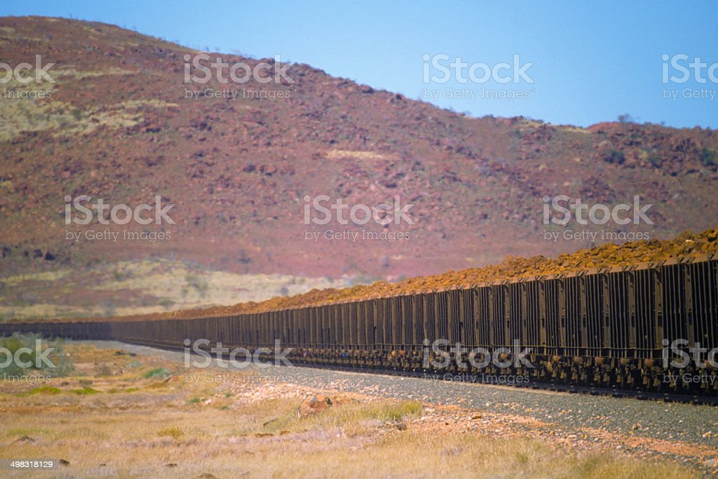 Heavy iron ore train in spectacular stony hills stock photo