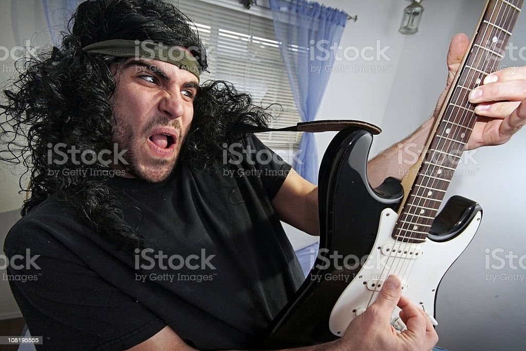 Heavy Metal Rocker in Bedroom with Electric Guitar royalty-free stock photo