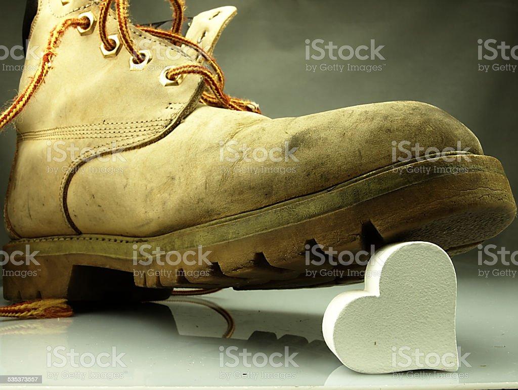 Heavy military boot trampling heart. stock photo