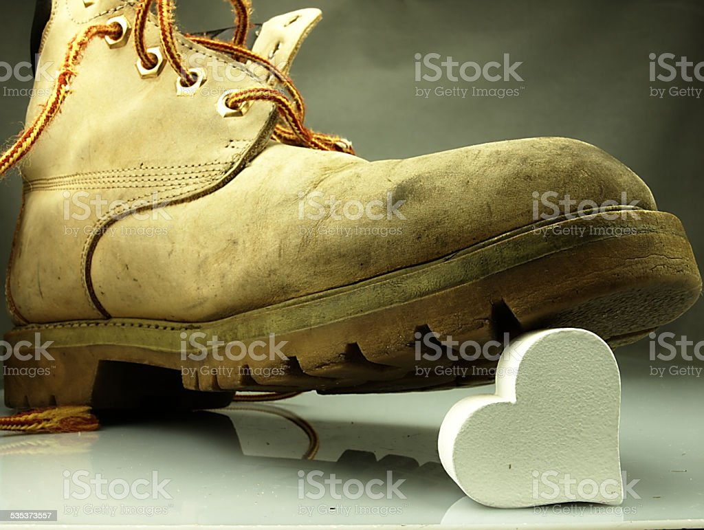 Heavy military boot trampling heart. stock photo