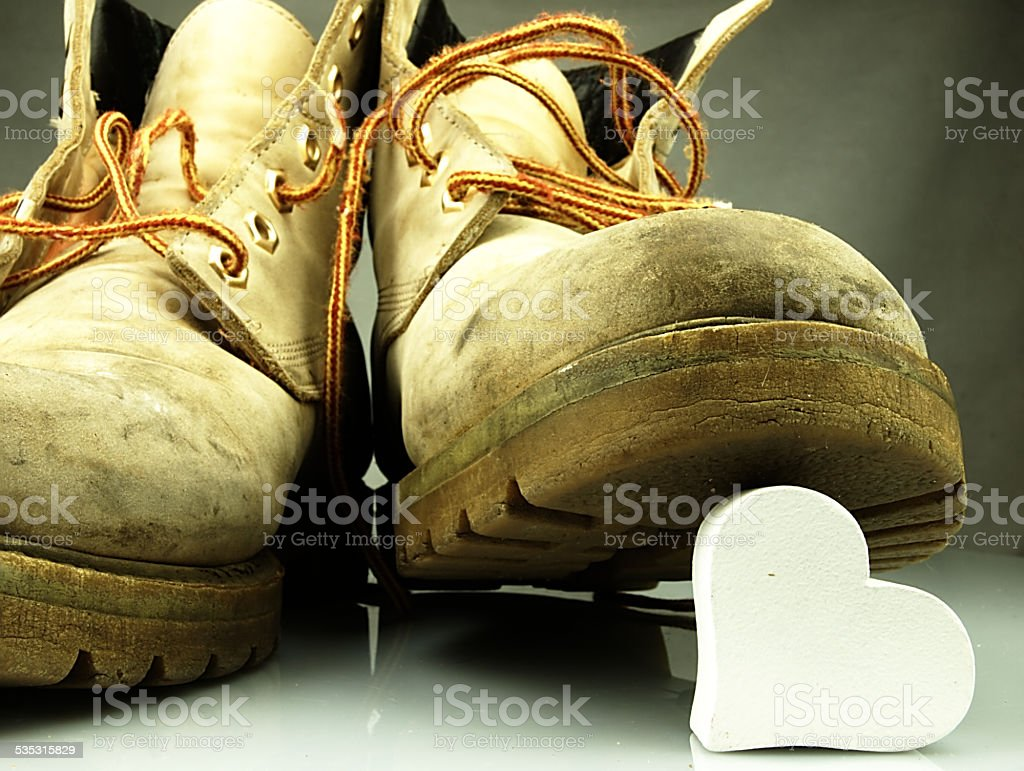 Heavy military boots trampling heart. stock photo