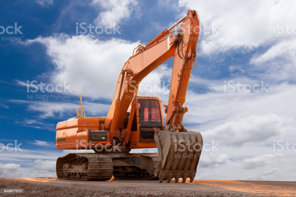 heavy organge excavator on a construction site against blue sky stock photo