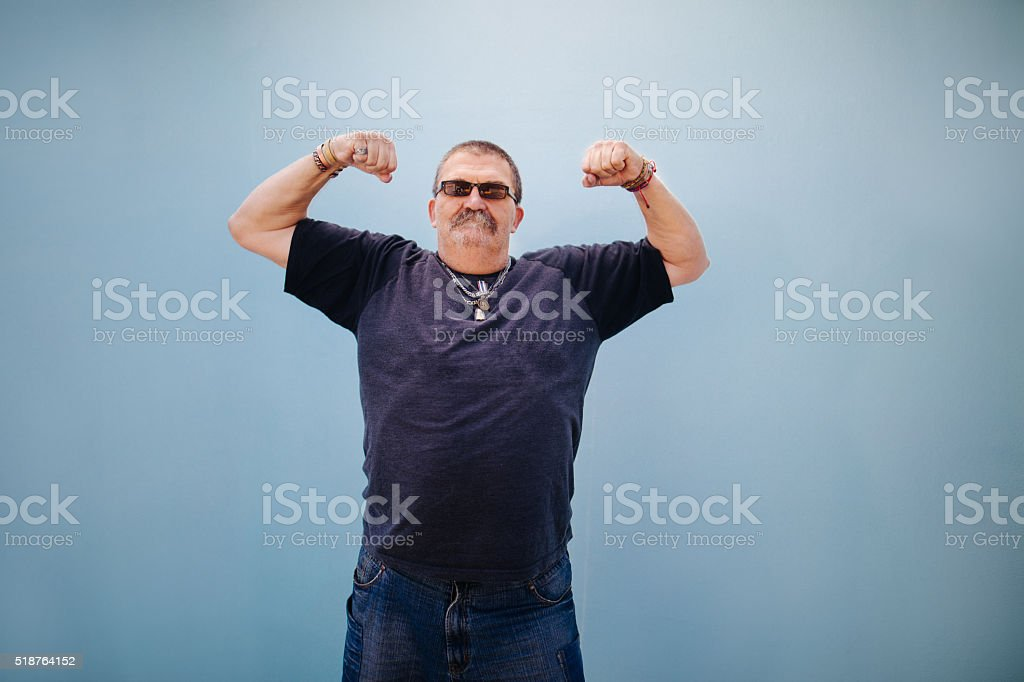 Heavy set older man showing his muscles stock photo
