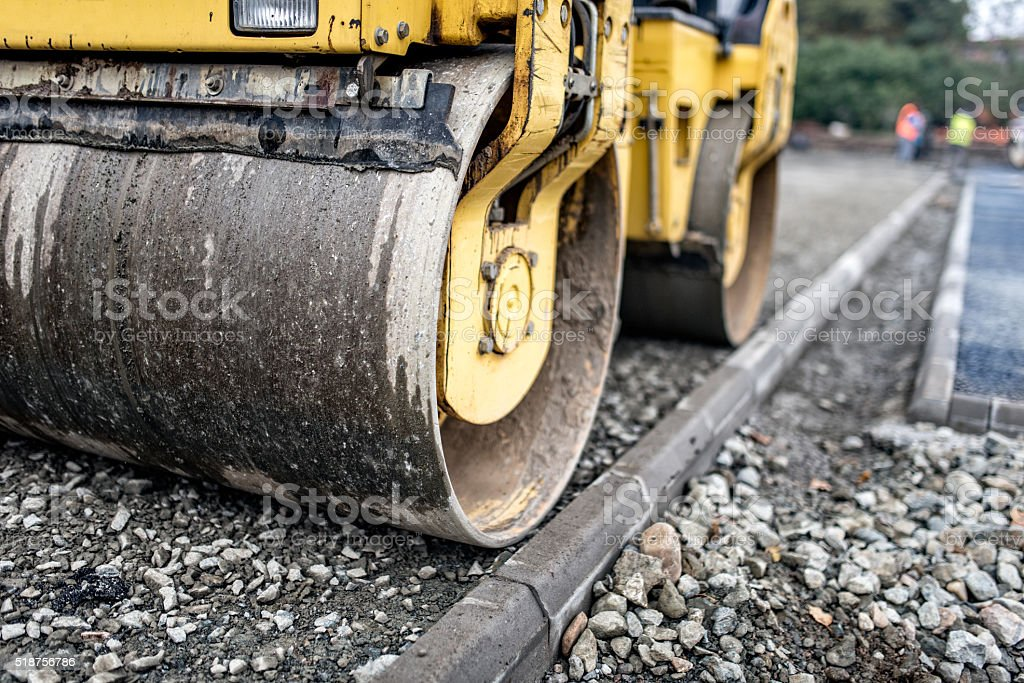 Heavy tandem road roller compacting layers of gravel stock photo