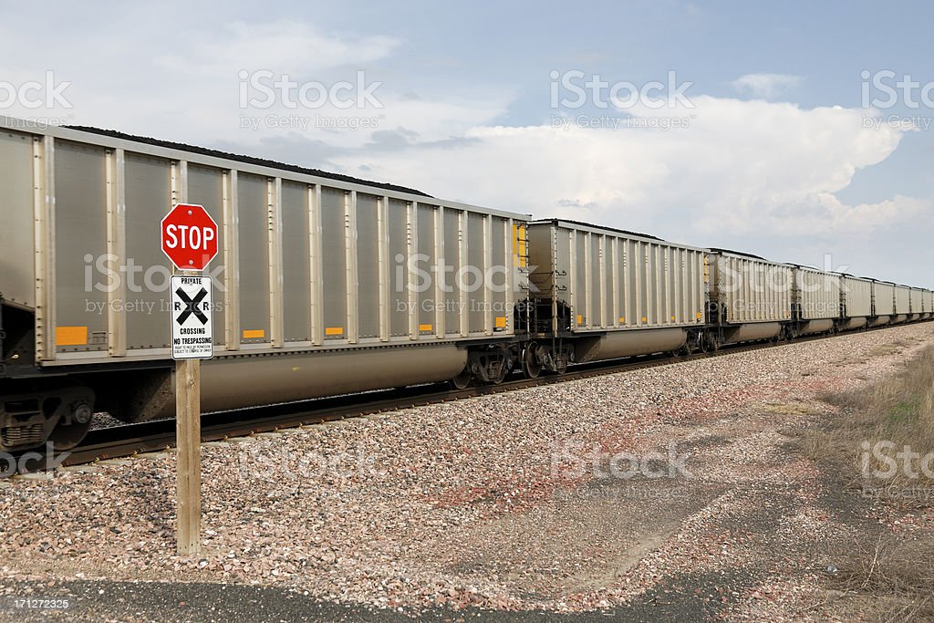 Heavy trainload of coal passes a crossing stop sign stock photo
