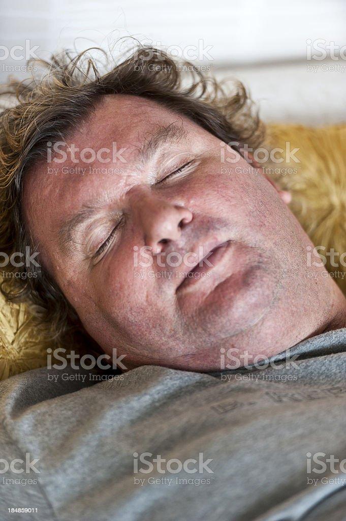 Heavyset man in grey shirt sleeps on saffron colored pillow stock photo