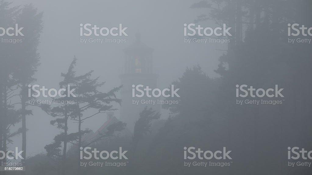 Heceta Head lighthouse in the fog stock photo