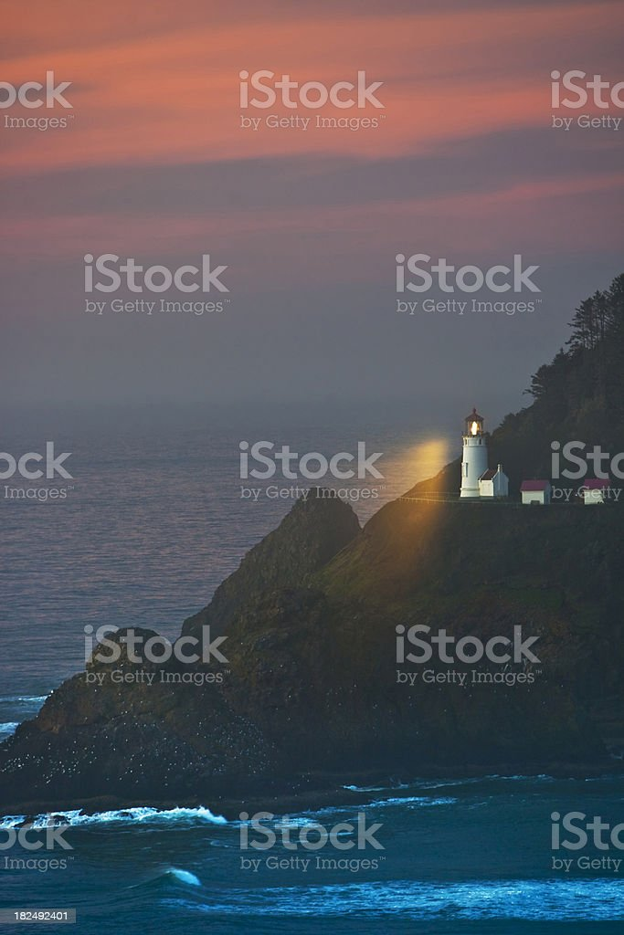 Heceta Head Lighthouse vertical shines light into the  night stock photo