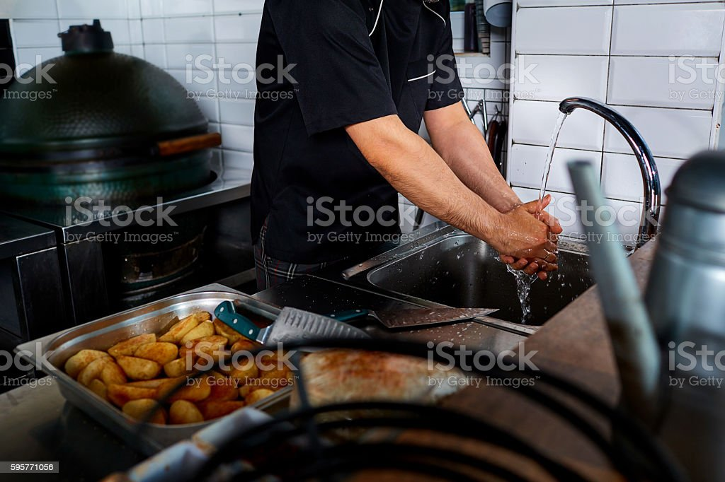 Ð¡hef washing his hands prior to preparing the cooking. stock photo