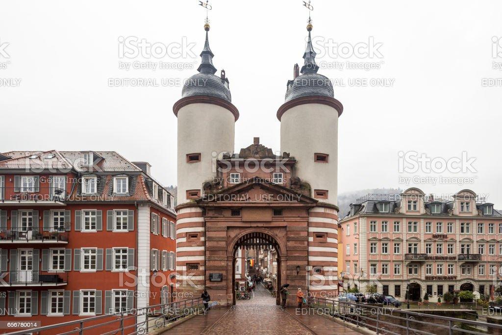Heidelberg Old Bridge Towers with surrounding European styled buildings, wet sett bridge paving on autumn gray day stock photo