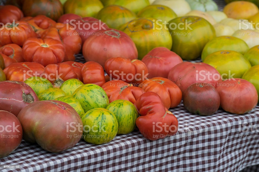 Heirloom tomatoes for sale on a farm stand table stock photo