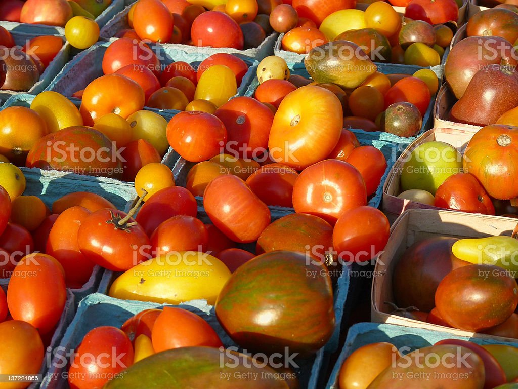 Heirloom tomatoes in baskets at farmers' market stock photo