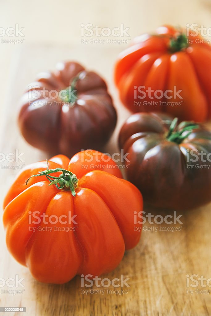 Heirloom tomatoes on wooden background stock photo