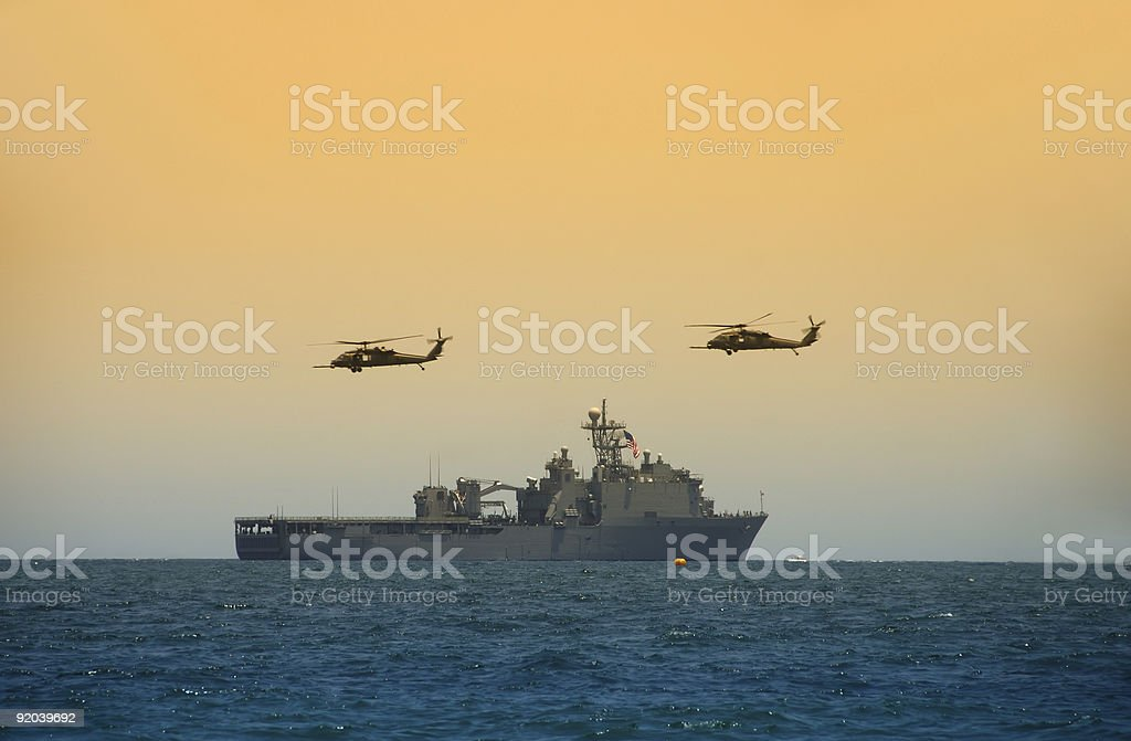 Helicopeters hovering over navy ship stock photo