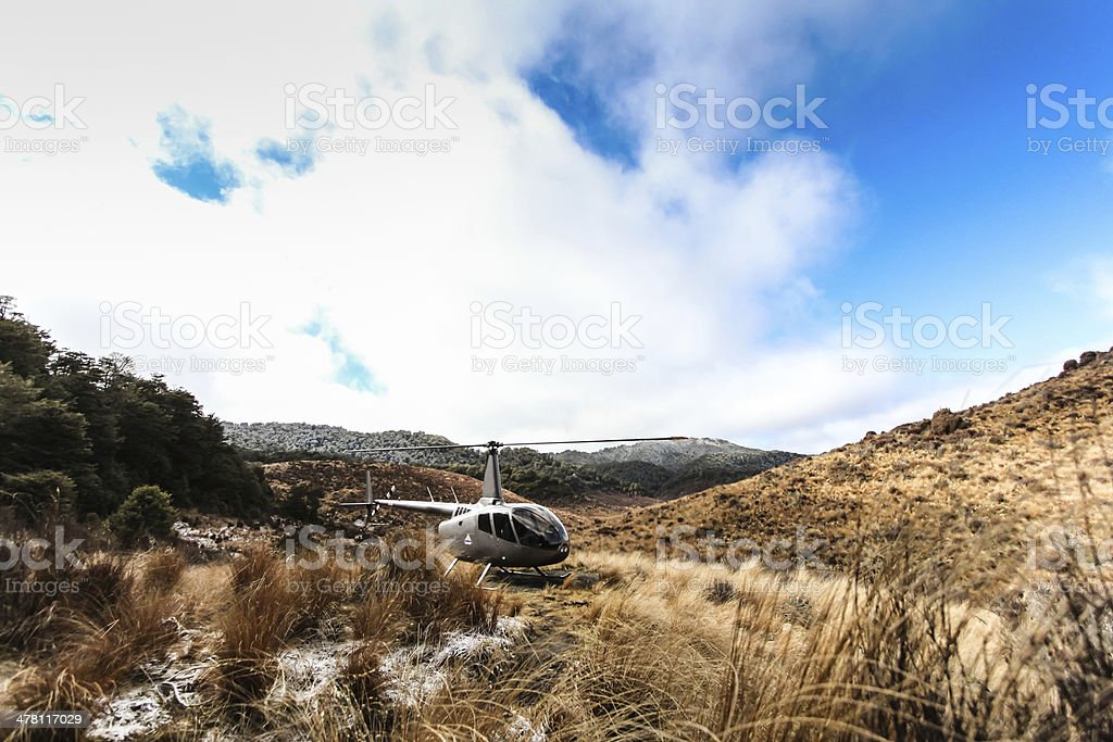 Helicopter about to take off from the tussock stock photo