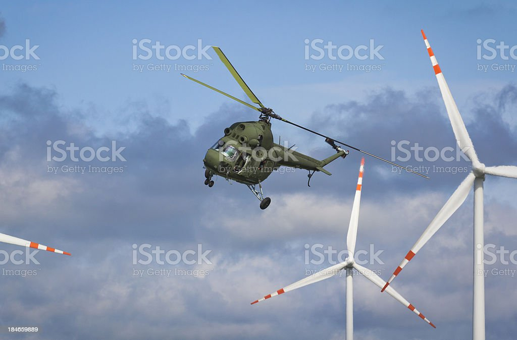 Helicopter against wind turbines stock photo