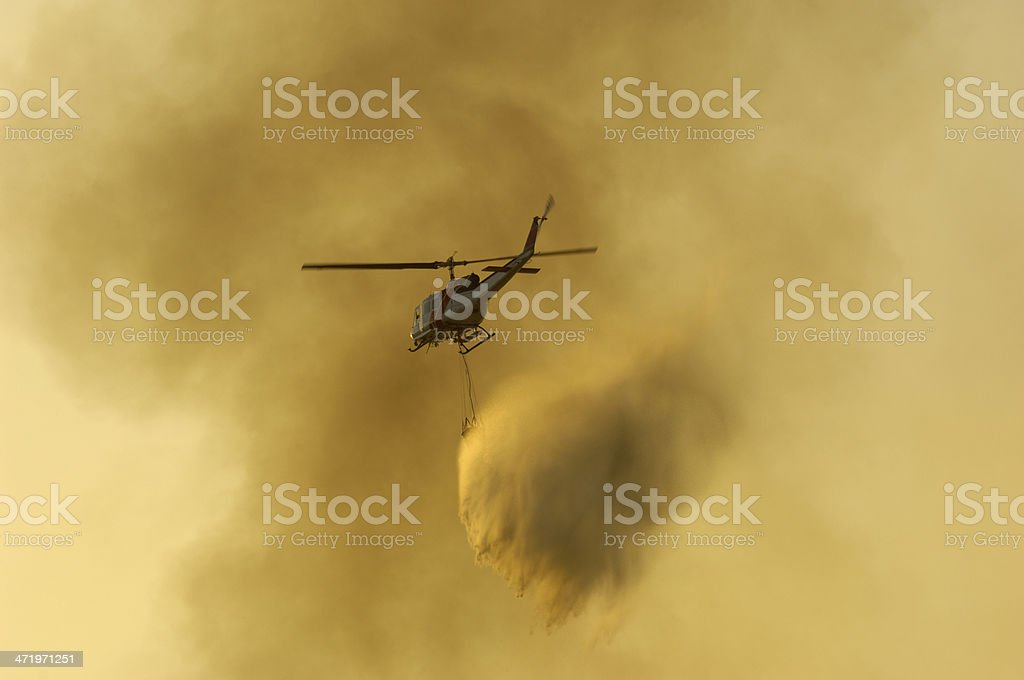 Helicopter Dropping Water on Out of Control Wildfire stock photo