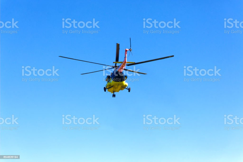 A helicopter flies off in the sky stock photo